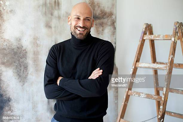 portrait of smiling man with crossed arms wearing black turtleneck - turtleneck stock pictures, royalty-free photos & images