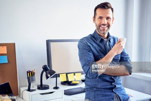 Portrait of smiling man with cup of coffee at desk in office