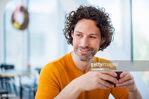 portrait of smiling man with curly brown hair holding cup of coffee - seitenblick stock-fotos und bilder