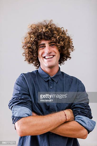 Portrait of smiling man with curly hair and crossed arms