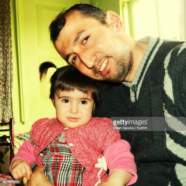 Portrait Of Smiling Man With Cute Daughter At Home