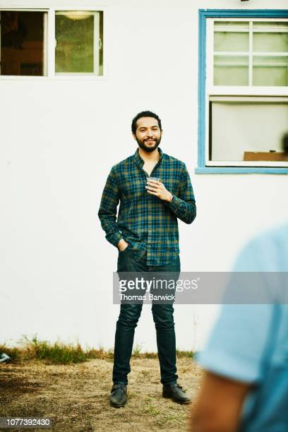 portrait of smiling man with drink standing in backyard during party - checked pattern stock pictures, royalty-free photos & images