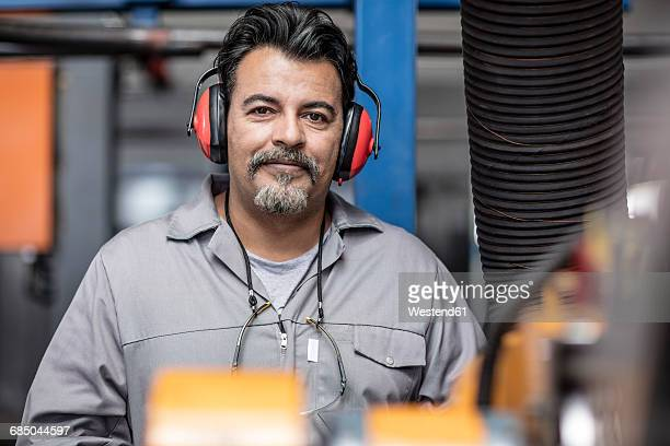 portrait of smiling man with earmuffs in factory - ear protection stock pictures, royalty-free photos & images