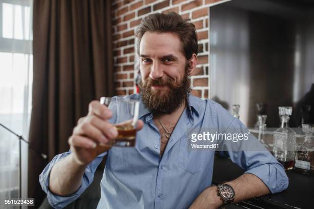 portrait of smiling man with glass of whiskey at home - brindisi bicchieri foto e immagini stock