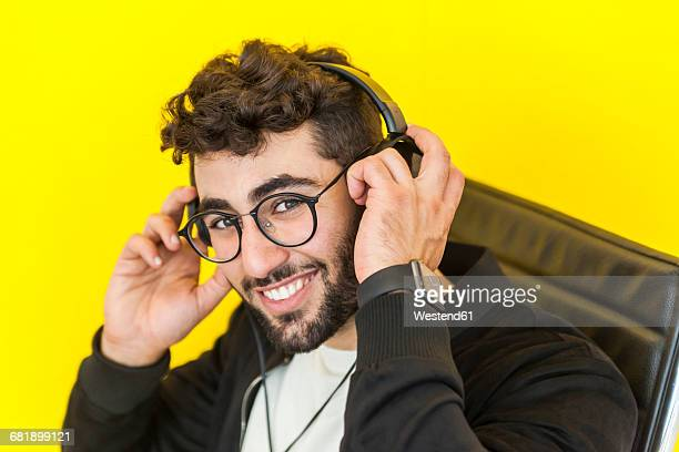 Portrait of smiling man with glasses putting on headphones