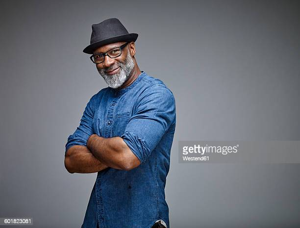 portrait of smiling man with grey beard wearing spectacles and hat - gray hat stock pictures, royalty-free photos & images