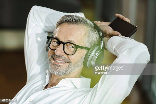 Portrait of smiling man with grey hair and beard listening music with headphones