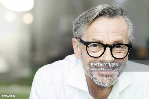 portrait of smiling man with grey hair and beard wearing spectacles - variable schärfentiefe stock-fotos und bilder