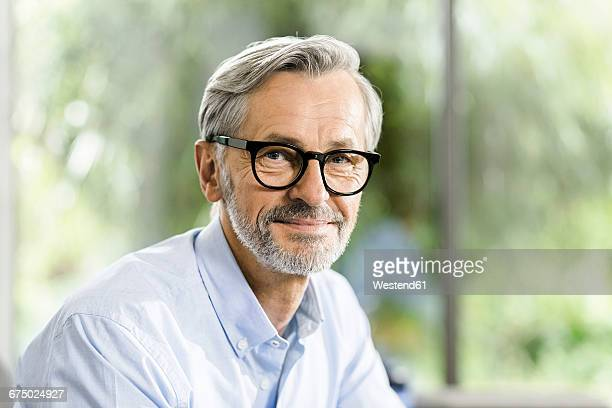Portrait of smiling man with grey hair and beard wearing spectacles