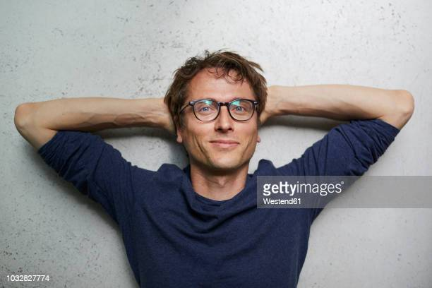 portrait of smiling man with hands behind head wearing glasses - tevreden stockfoto's en -beelden