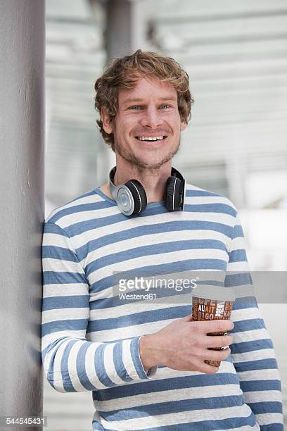 Portrait of smiling man with headphones and coffee to go