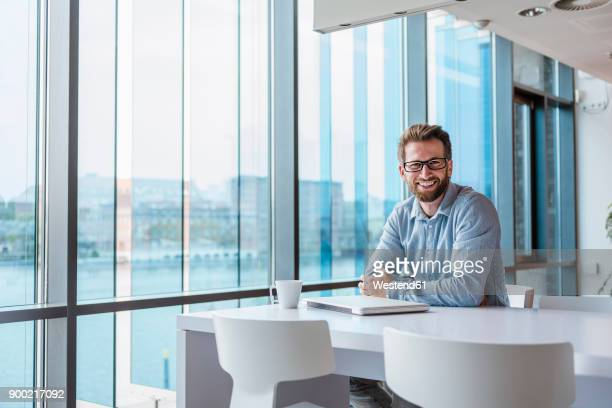 Portrait of smiling man with laptop and cup of coffee sitting in modern office