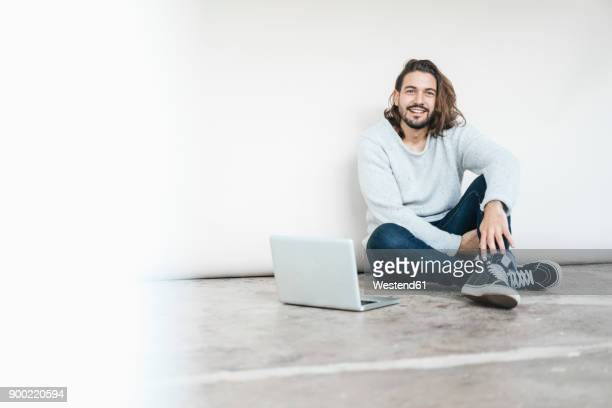Portrait of smiling man with laptop sitting on the floor