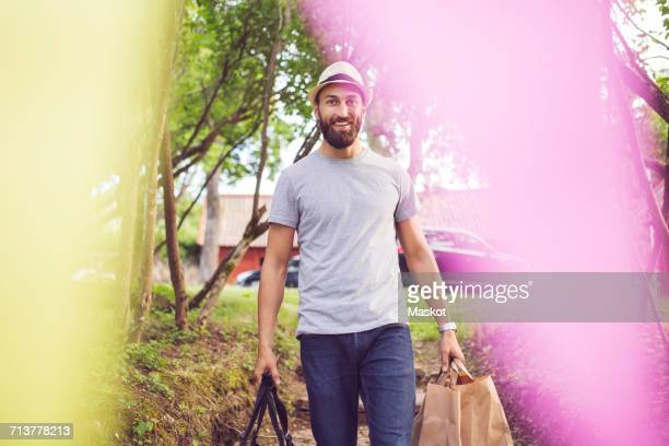 Portrait of smiling man with luggage on steps at back yard
