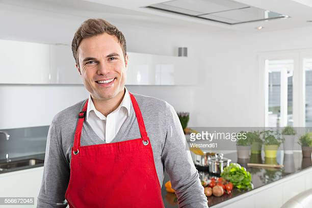Portrait of smiling man with red apron in kitchen