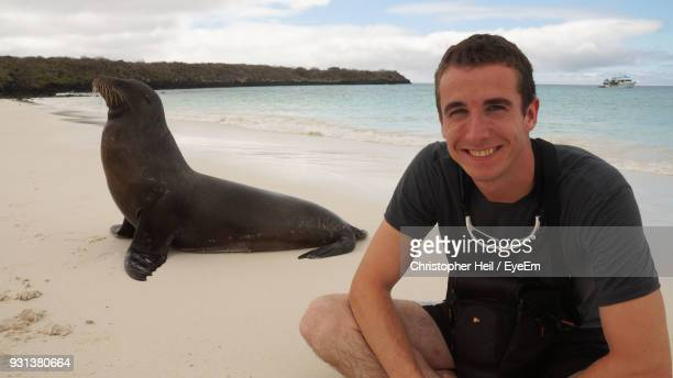 portrait of smiling man with sea lion at beach against sky - puerto ayora stock pictures, royalty-free photos & images