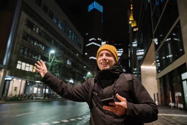 Portrait of smiling man with smartphone haling taxi at night, Frankfurt, Germany