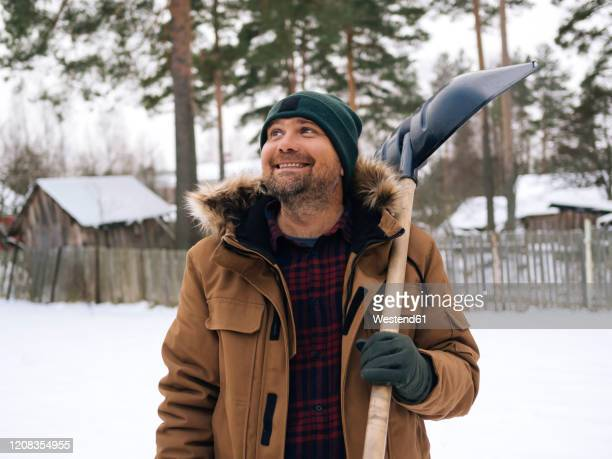 portrait of smiling man with snow shovel looking up - snow shovel stock pictures, royalty-free photos & images
