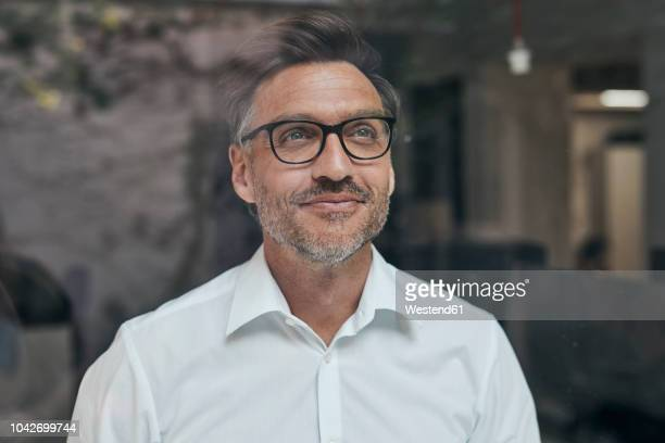 portrait of smiling man with stubble behind windowpane wearing white shirt and glasses - looking through window stock pictures, royalty-free photos & images