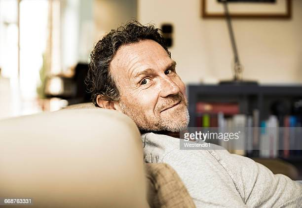 portrait of smiling man with stubble relaxing on the couch - gemütlich stock-fotos und bilder