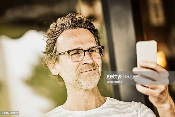 Portrait of smiling man with stubble taking selfie with smartphone