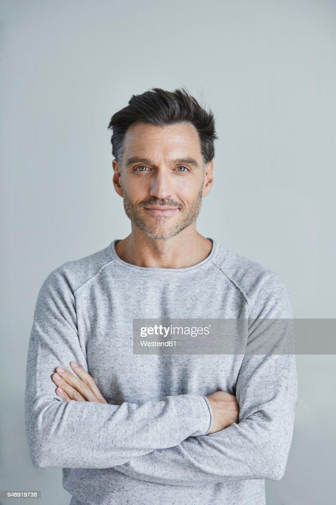 Portrait of smiling man with stubble wearing grey sweatshirt : Stock Photo
