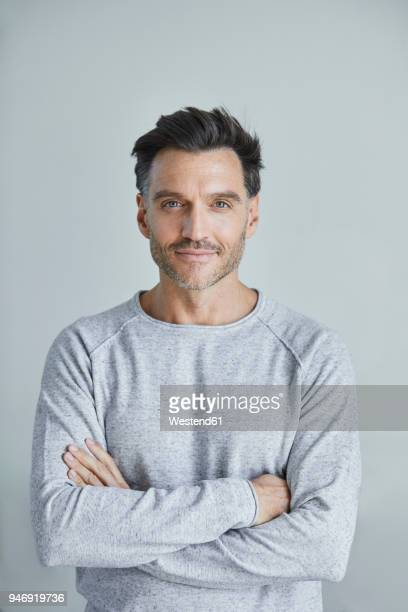 portrait of smiling man with stubble wearing grey sweatshirt - oudere mannen stockfoto's en -beelden