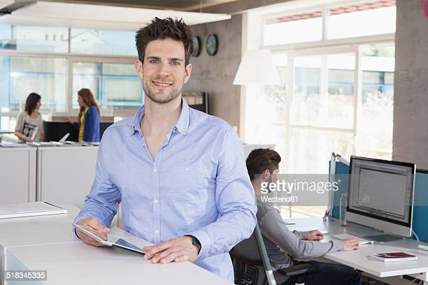 Portrait of smiling man with tablet computer in the office