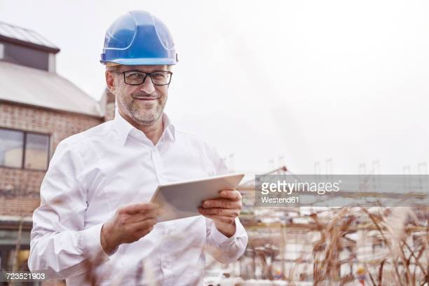 Portrait of smiling man with tablet wearing blue hart hat