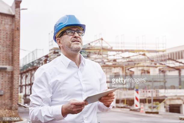 portrait of smiling man with tablet wearing blue hart hat - schutzhelm stock-fotos und bilder