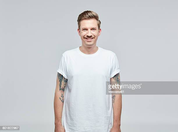 portrait of smiling man with tatoos on his arms wearing white t- shirt in front of grey background - maglietta foto e immagini stock