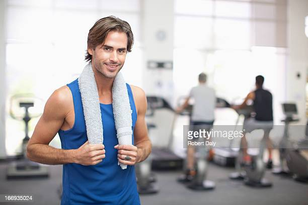 Portrait of smiling man with towel around neck in gymnasium