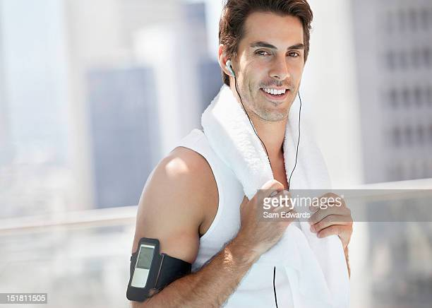 Portrait of smiling man with towel around neck listening to mp3 player on urban balcony