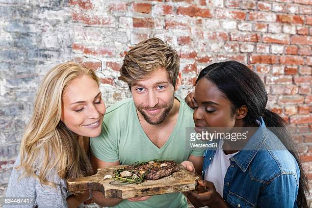 Portrait of smiling man with two women holding board with steak