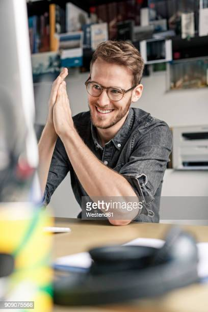 portrait of smiling man working at desk at home - vertikal stock-fotos und bilder
