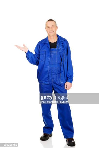 Portrait Of Smiling Manual Worker Gesturing Against White Background