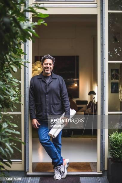 portrait of smiling mature architect with blueprint standing in doorway - architekturberuf stock-fotos und bilder