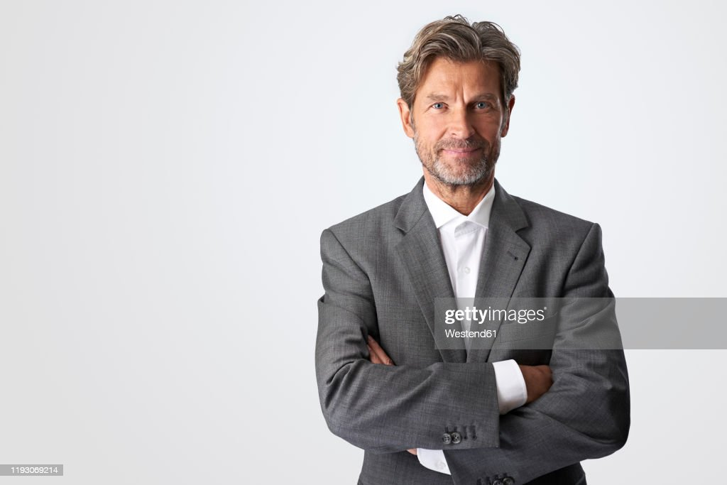 Portrait of smiling mature businessman against light background : Stock-Foto