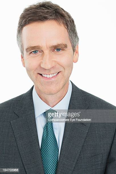 "portrait of smiling mature businessman, close up - ""compassionate eye"" stockfoto's en -beelden"