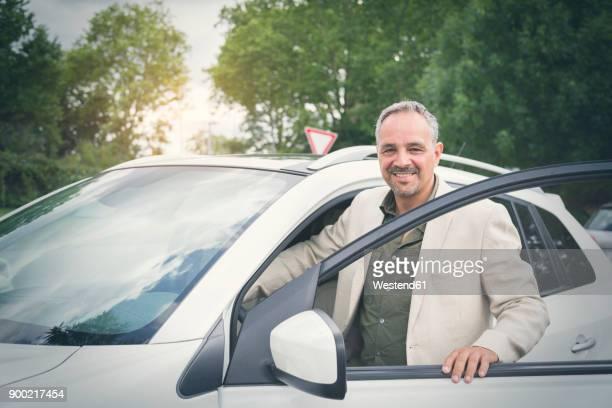 Portrait of smiling mature businessman entering his car