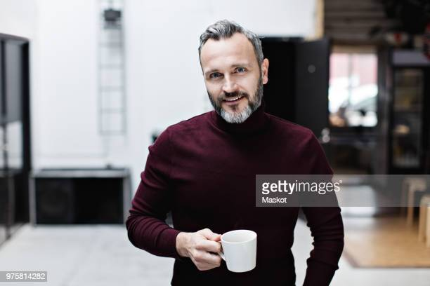 portrait of smiling mature businessman having coffee while standing at creative office - variable schärfentiefe stock-fotos und bilder