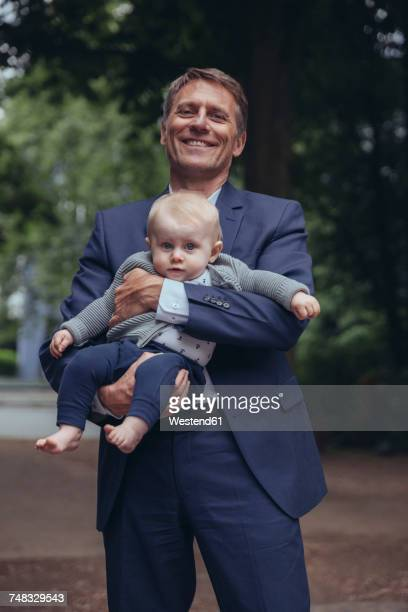 Portrait of smiling mature businessman holding baby boy outdoors