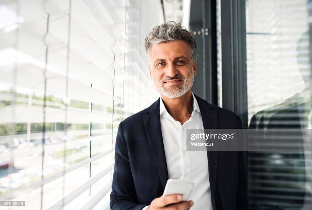 Portrait of smiling mature businessman holding cell phone at outside sunblind : Stock Photo