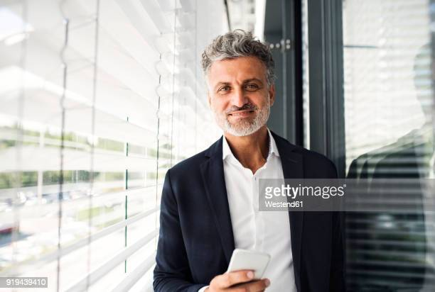 portrait of smiling mature businessman holding cell phone at outside sunblind - einzelner mann über 40 stock-fotos und bilder