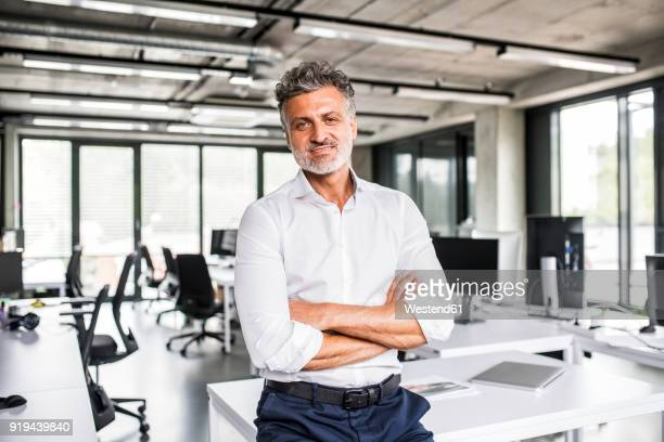 portrait of smiling mature businessman in office - rolled up sleeves stock photos and pictures