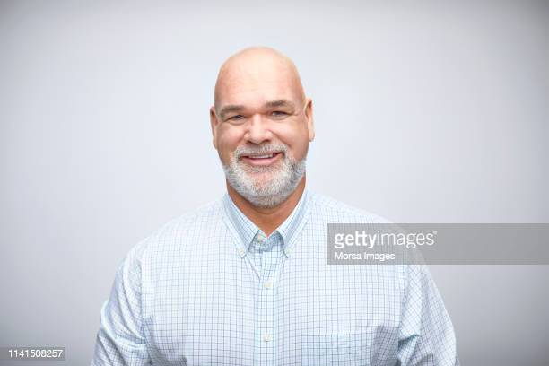 portrait of smiling mature businessman in studio - completamente calvo foto e immagini stock