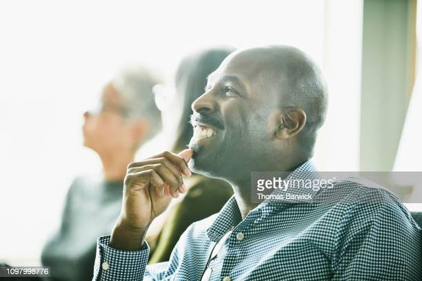 Portrait of smiling mature businessman listening during meeting with coworkers