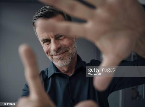 portrait of smiling mature businessman making a finger frame - bildschärfe stock-fotos und bilder