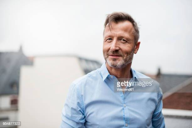 portrait of smiling mature businessman on roof terrace - eine person stock-fotos und bilder