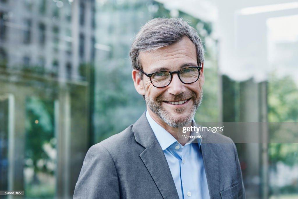 Portrait of smiling mature businessman outdoors : Stock Photo